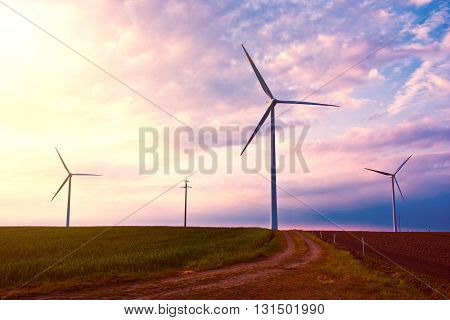 Windmills on the windfarm agriculture land. Field and sky at sunset. Green renewable alternative energy source.