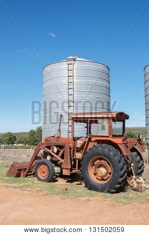 Antique rusted tractor with bulk storage silo on farmland with native plants under a blue sky in Western Australia.