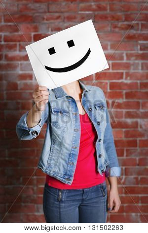Woman showing a happy emoticon in front of face against a brick wall background