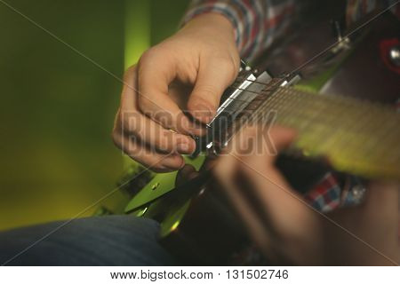 Young man playing electric guitar on lighted foggy background