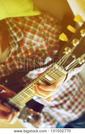 Young man playing electric guitar on grey sofa at home
