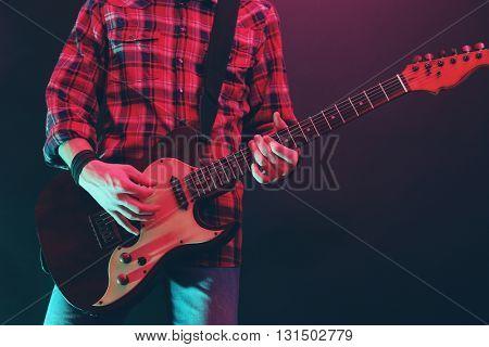 Man with guitar on dark foggy background