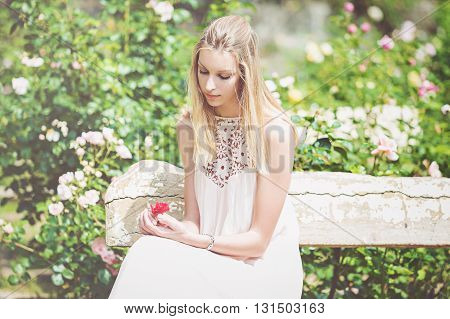 Portrait of beautiful natural young woman in the rose garden