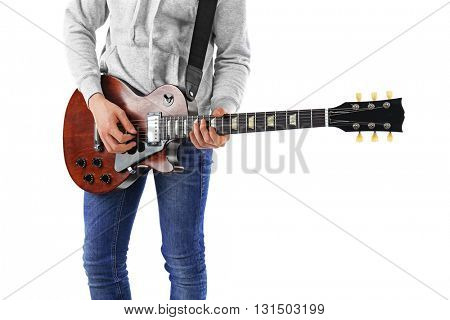 Young man in blue jeans playing electric guitar, isolated on white