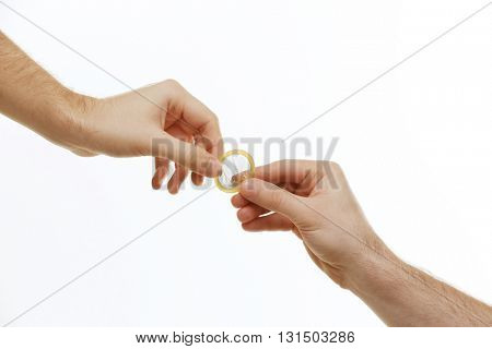 One man giving a condom to another man isolated on white