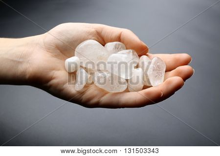 Woman holding semiprecious stones in her hand on dark grey background