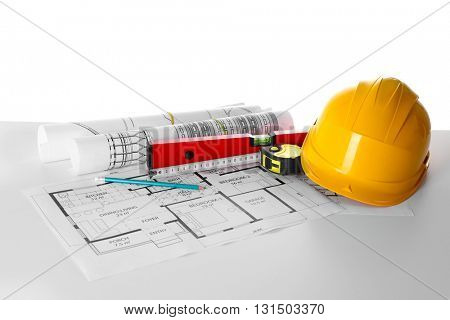 Construction blueprints with tools and helmet on white background