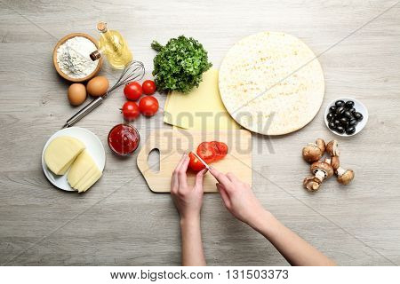 Female hands cooking pizza on wooden table, closeup