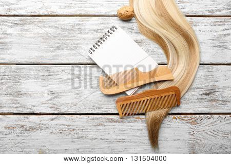 Two combs with blond curl on wooden table, copy space