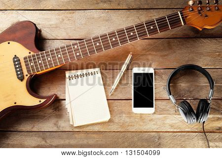 Guitar and smartphone on wooden background