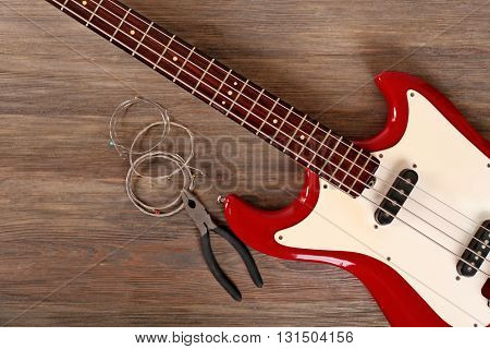 Electric guitar with pliers and strings on wooden background