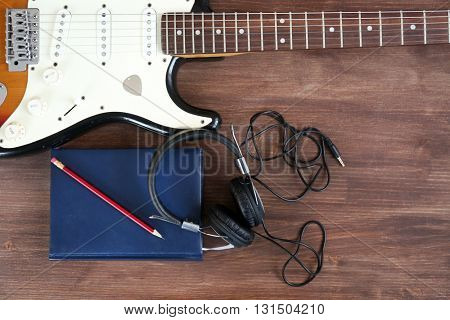 Guitar with headphones on wooden surface closeup