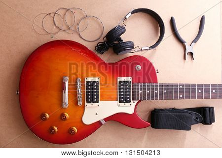 Electric guitar with headphones, pliers and strings on beige background