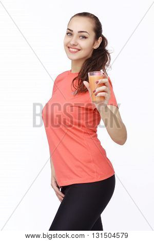 Portrait of smiling fitness young woman posing with glass of juice