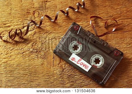 Retro audio cassette with tape in shape of heart on wooden background
