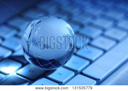 Crystal globe on laptop keyboard,  close up