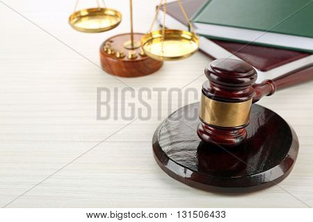 Gavel with books and scales on wooden background