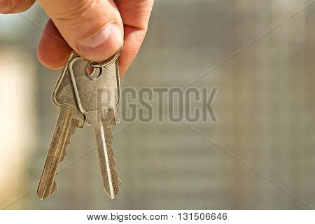 The keys to the apartment in hand on the background of houses