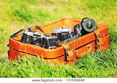 Modern and old cameras with leather suitcase on green grass outdoors