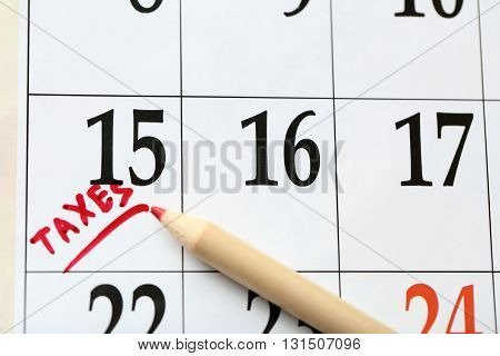 A red tax mark in the calendar on date of 15th with a pencil, close up