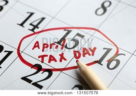 April tax day written and circled in a calender on date of 15th, close up
