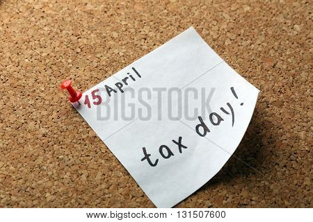 Tax day reminder on April of 15th pinned to the board, close up