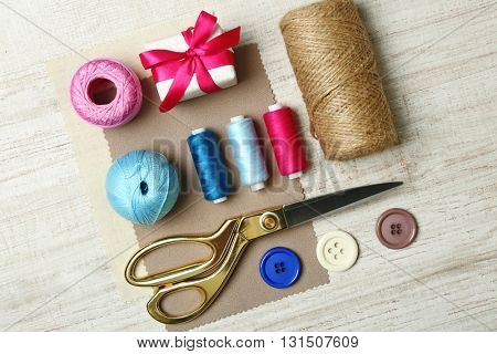 Sewing creative accessories on wooden table, top view