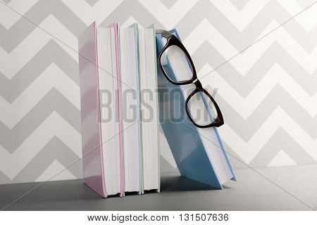 Books and eyeglasses on grey table against ornament wall, close up