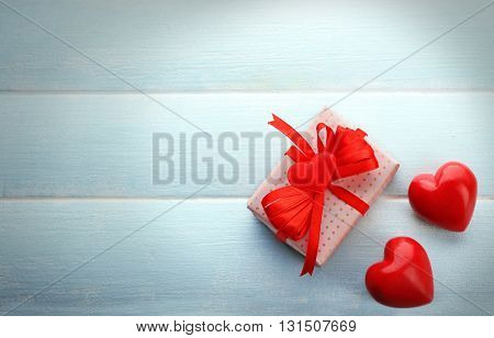 Gift box and decorative hearts on color wooden background