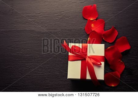 Gift box, rose petals and decorative hearts on wooden background