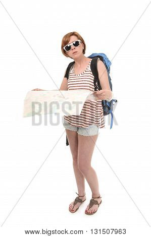 young attractive American tourist woman with red hair holding city map carrying backpacker rucksack and wearing shorts smiling happy isolated on white background looking lost and confused