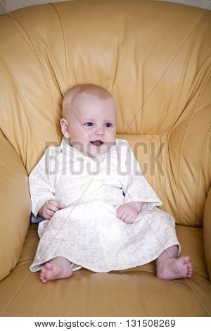 Little boy is sitting in a yellow leather chair