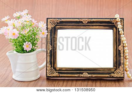 Flowers vase and vintage picture frame on wooden desktop saved clipping path