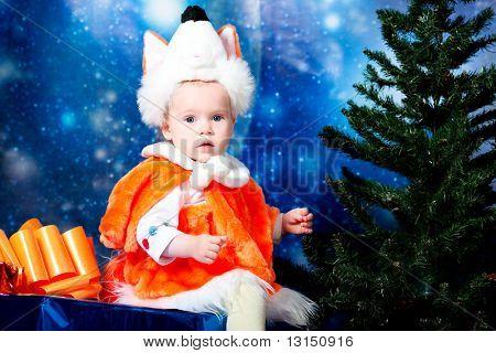 Christmas child sitting on a big present against night stellar sky.