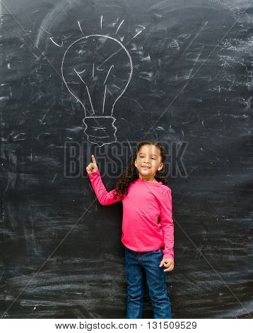 cute little girl pointing on a drawn lamp on chalky blackboard