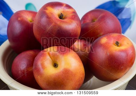Nectarines Isolated and overflowing in a white bowl.