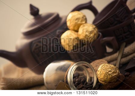 Italian chocolate sweets with Chinese tea set on the wooden table