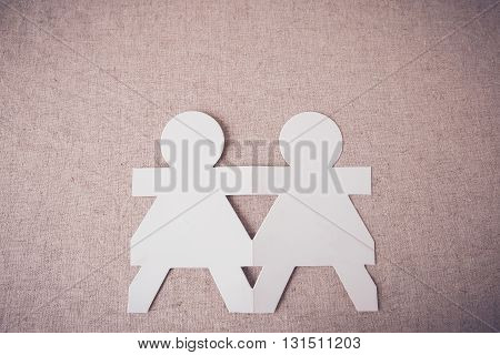 paper dolls holding hands on linen background,teamwork, friendship,eco concept