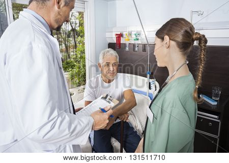 Patient Looking At Nurse While Doctor Holding Reports