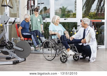 Doctor Holding Senior Woman's Leg In Wheelchair At Fitness Cente