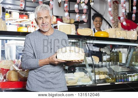 Senior Customer Holding Cheese While Saleswoman Working At Count