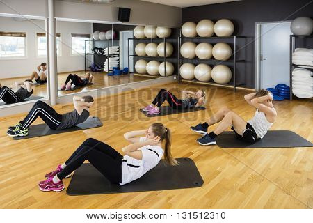 High Angle View Of Friends Doing Situps