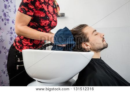 Hairdresser Wiping Male Customer's Hair In Salon