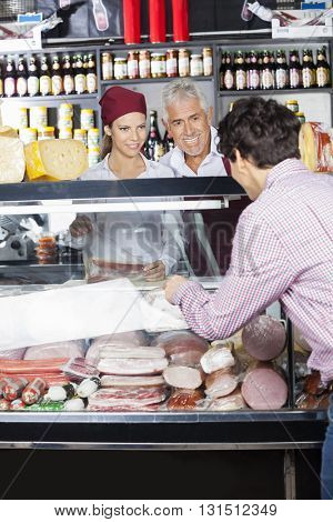Salespeople Assisting Male Customer In Buying Cheese