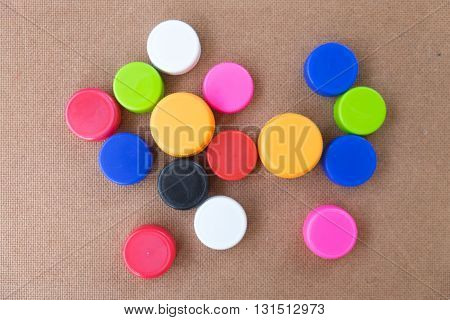 Colorful plastic bottle screw caps used on wood
