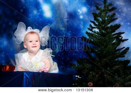 Christmas child sitting on a big present against night stellar sky.