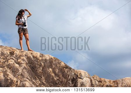 Woman with a photo camera enjoys the beauty of nature hiking in the mountain peak
