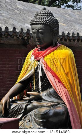 A buddha statue covered in robes at the Shaolin temple in Dengfeng city Henan Province China.