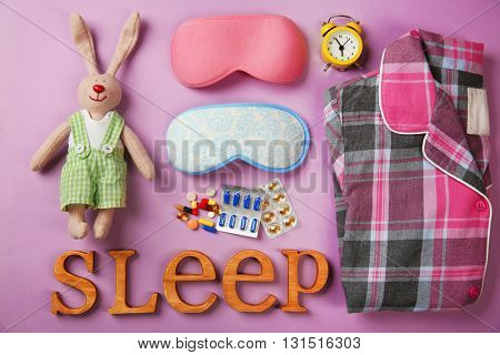 Insomnia concept. Sleeping accessories on purple background