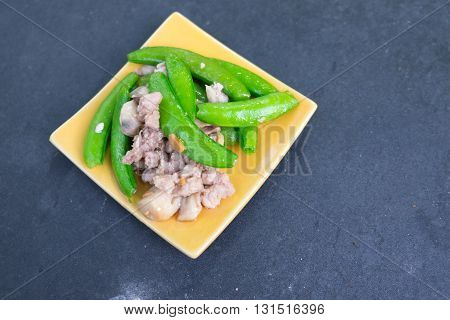 Stir fry sugar snap peas with pork on black wood